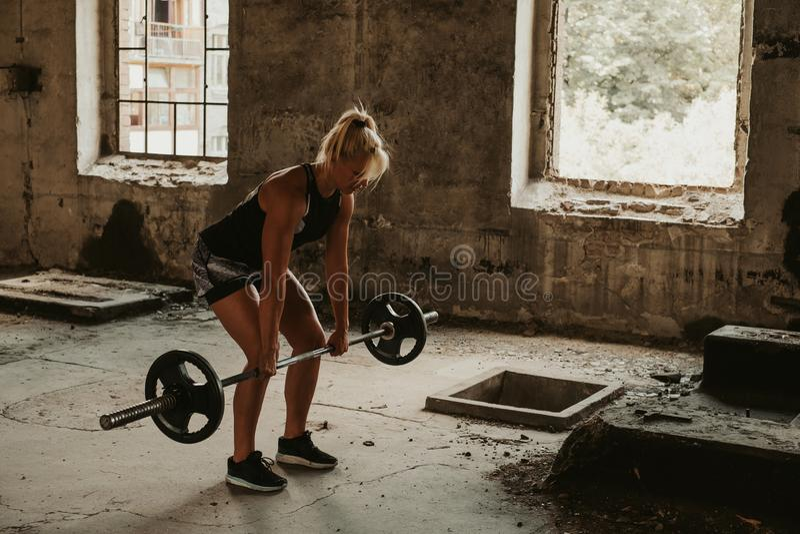 Femme sportive faisant le deadlift dans un vieux bâtiment photos libres de droits