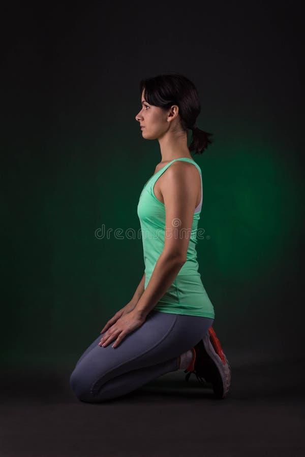 Femme sportive, femme de forme physique s'asseyant sur un fond foncé avec le contre-jour vert photo libre de droits