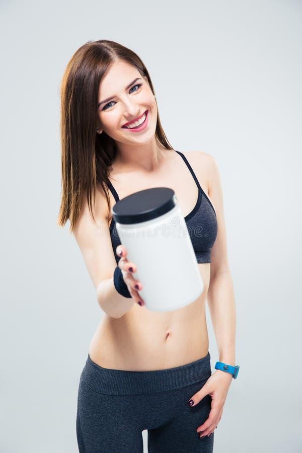 Femme sportive heureuse donnant le pot de protéine sur l'appareil-photo image libre de droits