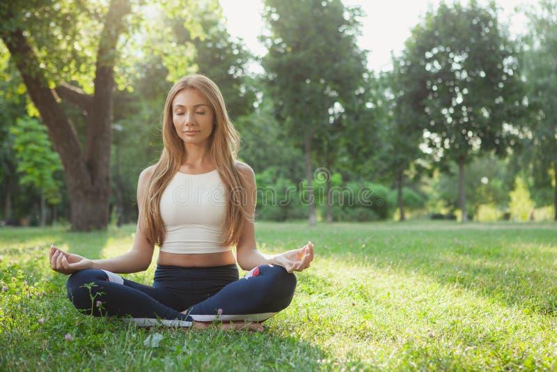 Femme sportive magnifique faisant le yoga au parc photo stock