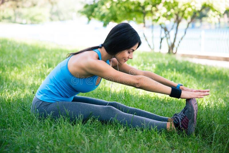 Femme sportive s'étirant sur l'herbe verte photo libre de droits
