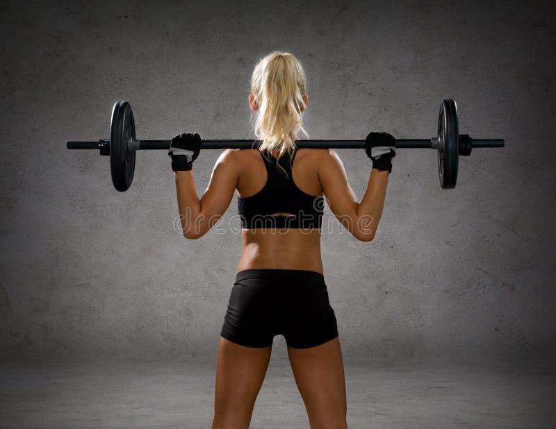 Femme sportive s'exerçant avec le barbell du dos photographie stock