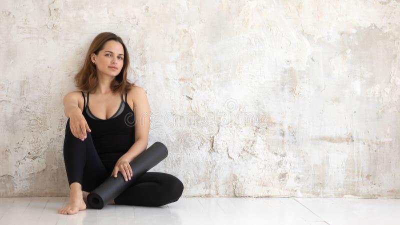 Femme sportive se reposant après maigre de séance d'entraînement contre le mur grunge beige photo libre de droits