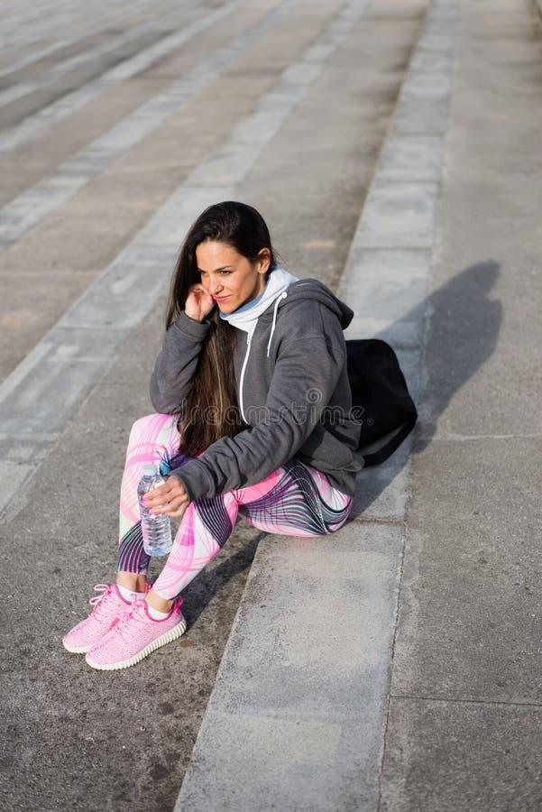 Femme sportive se reposant après séance d'entraînement pour l'eau potable  photo stock