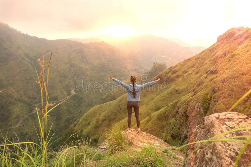 Femme sportive se tenant avec les bras augmentés sur oh la colline supérieure regardant le lever de soleil photo stock