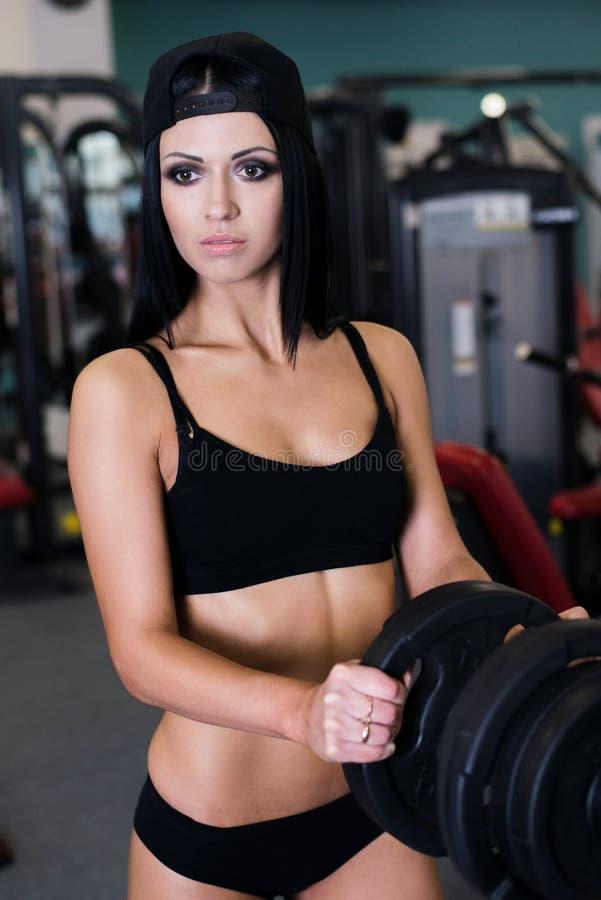 Femme sportive sexy faisant l'exercice de forme physique de puissance au gymnase de sport Belle fille établissant dans le gymnase image libre de droits