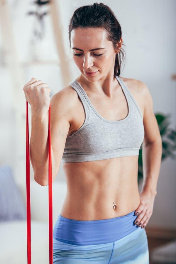 Femme sportive sportive s'exerçant avec la bande en caoutchouc photos stock