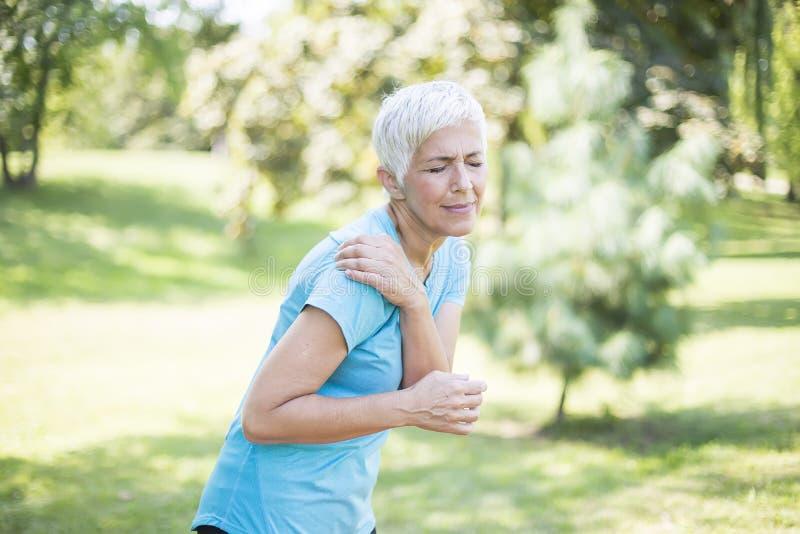Femme sportive supérieure ayant la douleur d'épaule photographie stock