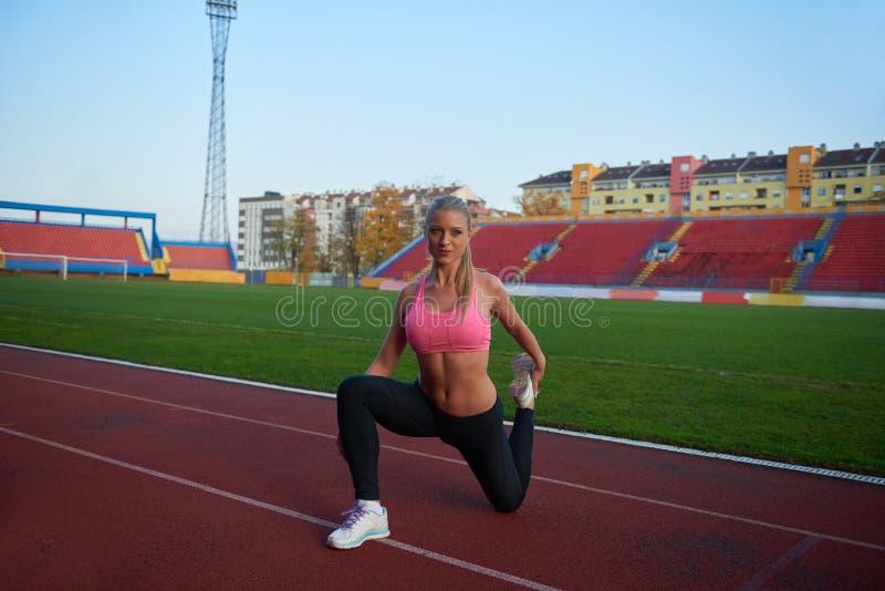 Femme sportive sur la voie de course sportive photographie stock libre de droits