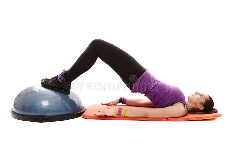 Femme sportive travaillant ses jambes et fond sur une boule de bosu photo libre de droits