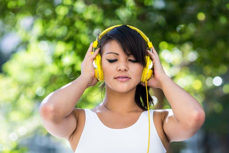 Femme sportive utilisant les écouteurs jaunes et appréciant la musique avec des yeux fermés photos stock