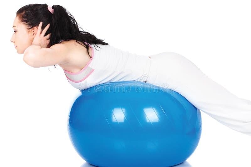 Femme streching sur la bille bleue images stock