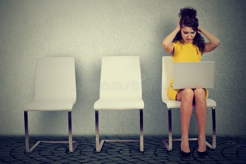 Femme stressante s'asseyant sur la chaise avec l'ordinateur portable photo libre de droits