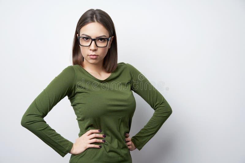 Femme stricte en verres se tenant regardants la caméra avec le regard intense photo libre de droits