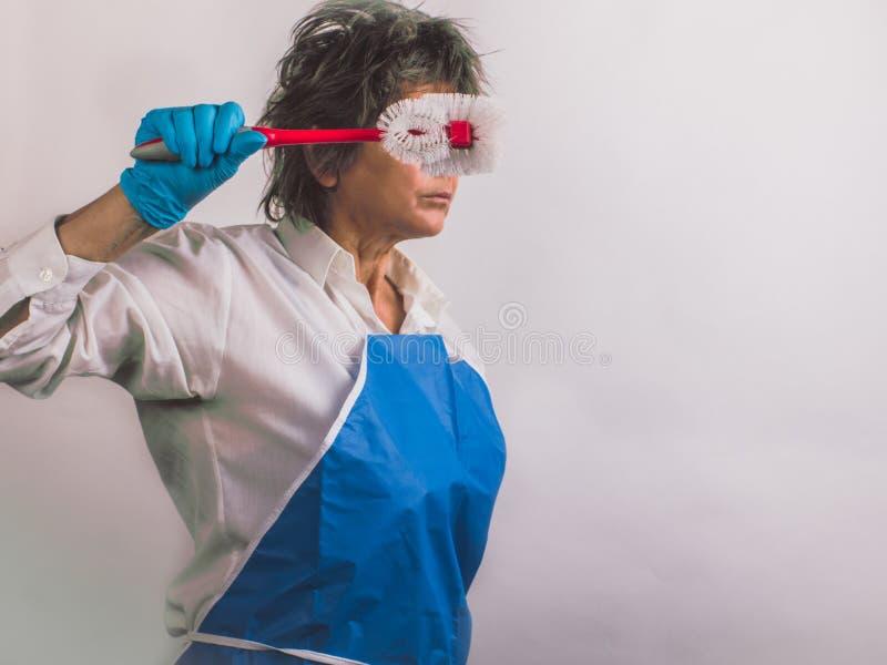 Femme stricte supérieure dans le profil dans les gants en caoutchouc bleus protecteurs photographie stock