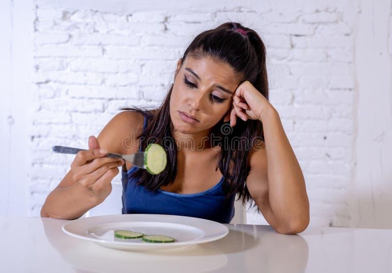 Femme suivante un régime déprimée tenant des gens regardant le petit légume vert du plat vide image stock