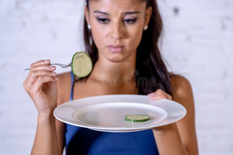Femme suivante un régime déprimée tenant des gens regardant le petit légume vert du plat vide photos libres de droits