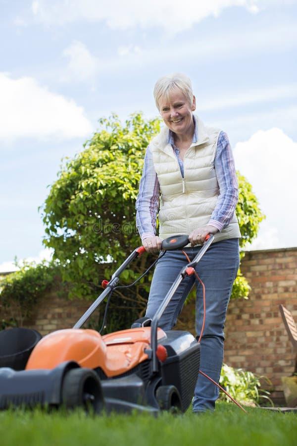 Femme supérieure à l'aide de la tondeuse à gazon électrique pour couper l'herbe à la maison images libres de droits