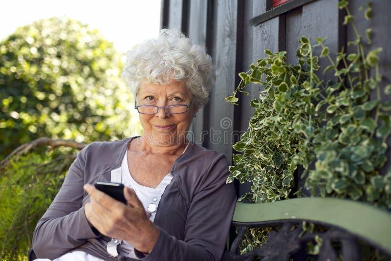 Femme supérieure à l'aide du téléphone portable image libre de droits