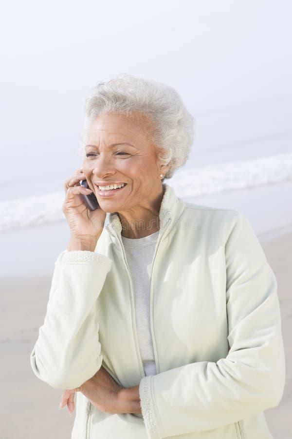 Femme supérieure à l'appel à la plage photo stock
