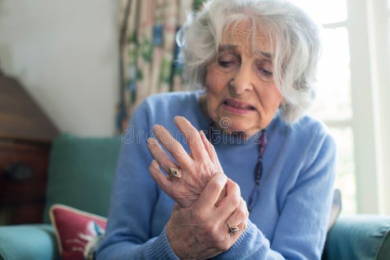 Femme supérieure à la maison souffrant avec l'arthrite photo libre de droits