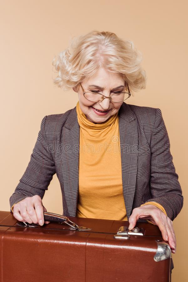 femme supérieure à la mode dans des lunettes fermant la valise de vintage photographie stock