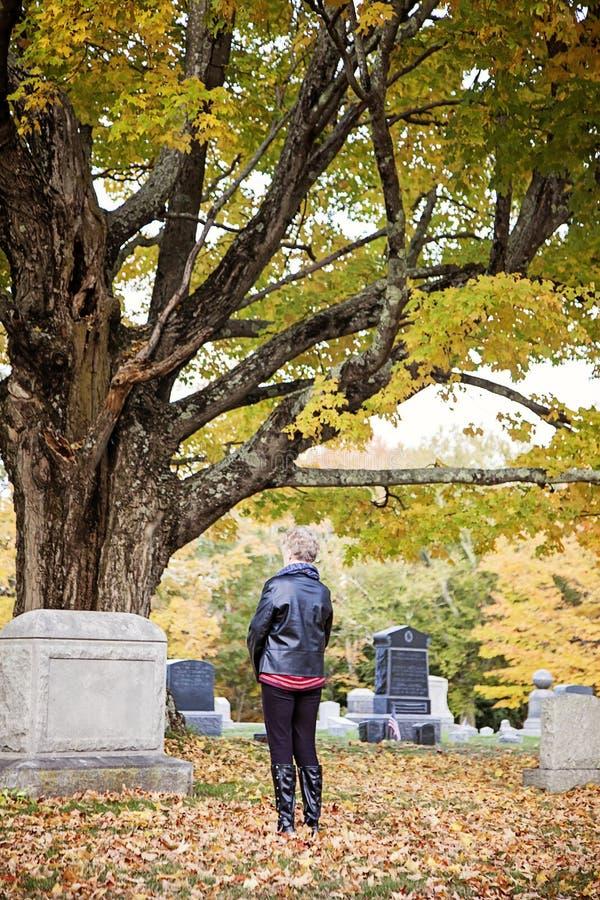 Femme supérieure à la tombe dans le cimetière image stock