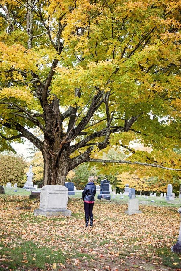 Femme supérieure à la tombe dans le cimetière images stock