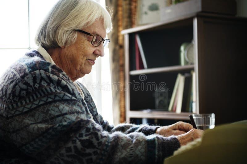 Femme supérieure écrivant une lettre photos libres de droits