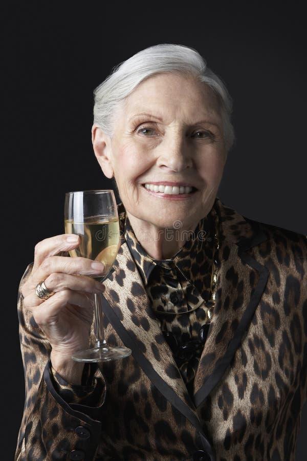 Femme supérieure élégante avec le verre à vin photographie stock