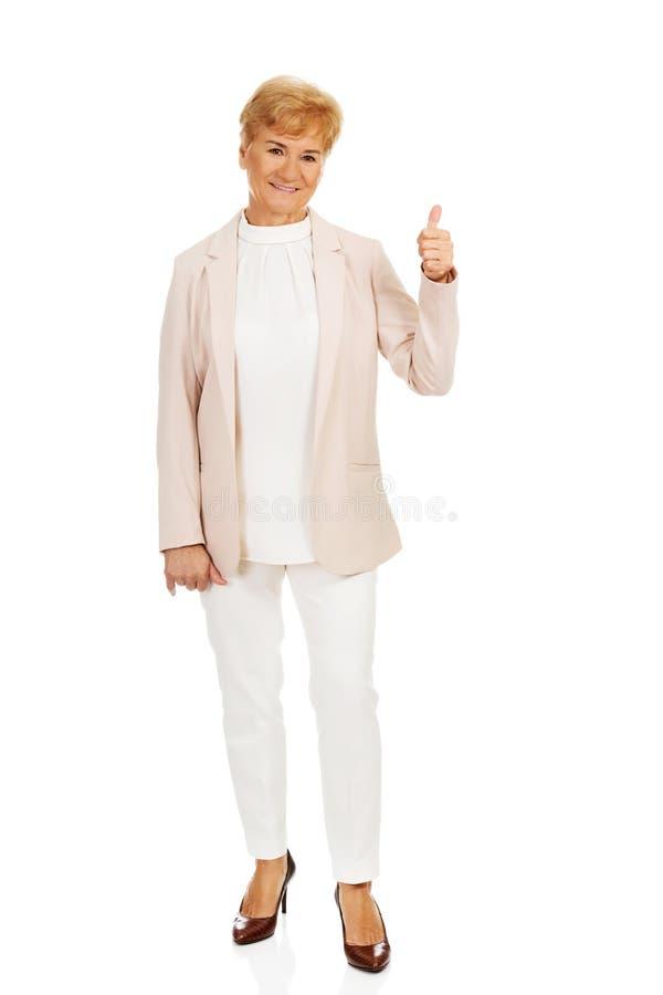 Femme supérieure élégante de sourire montrant le pouce  images stock