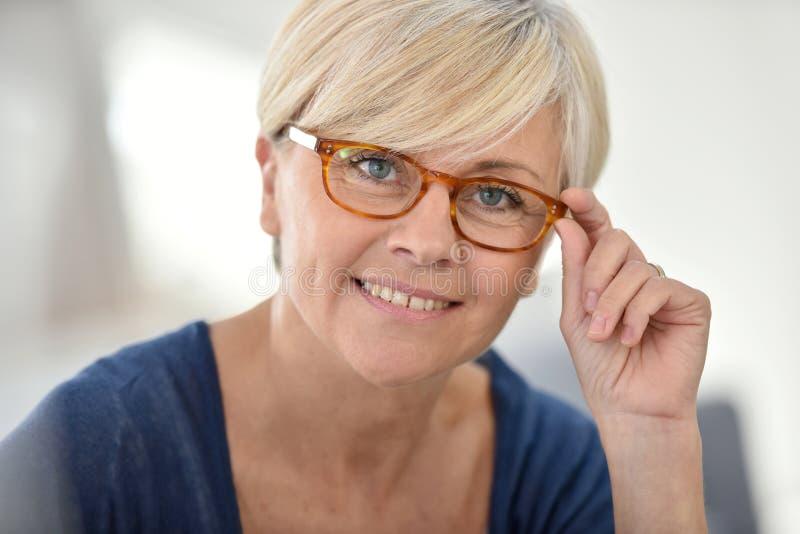 Femme supérieure élégante utilisant les lunettes à la mode image stock