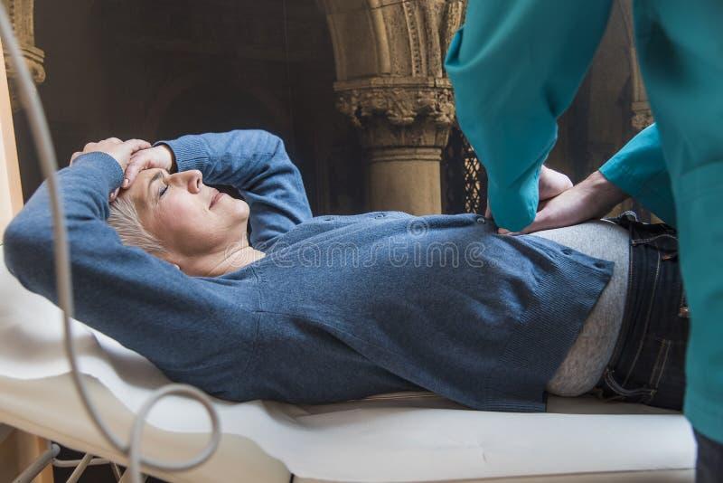 Femme supérieure éprouvant la douleur abdominale image stock