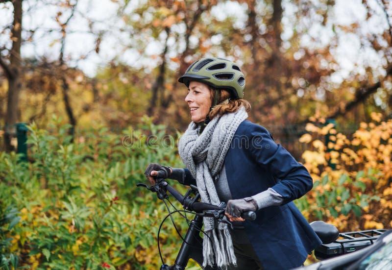 Femme supérieure active avec l'electrobike faisant un cycle dehors en parc photos stock