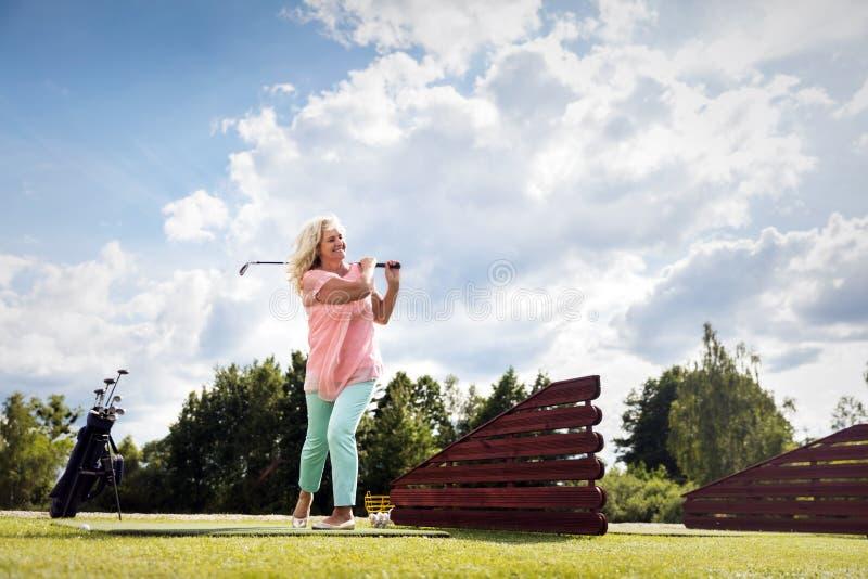 Femme supérieure active jouant le golf images stock