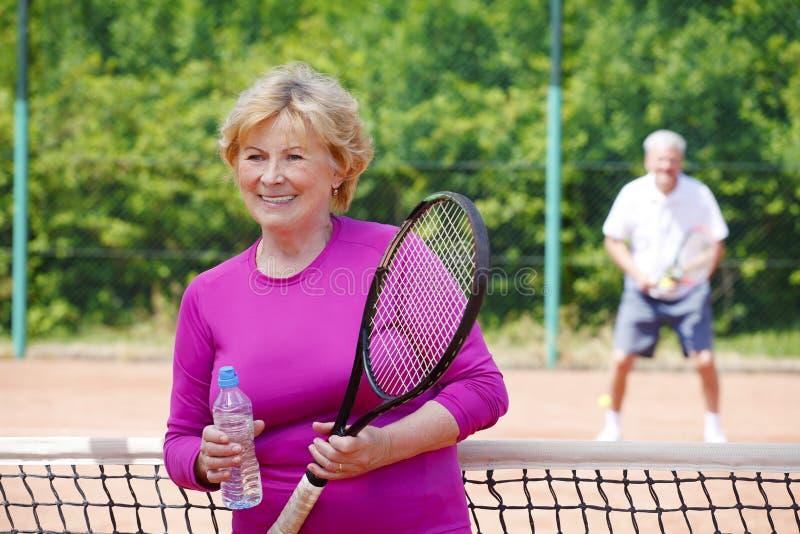 Femme supérieure active jouant le tennis image stock