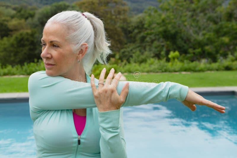 Femme supérieure active s'exerçant près du poolside dans l'arrière-cour photographie stock