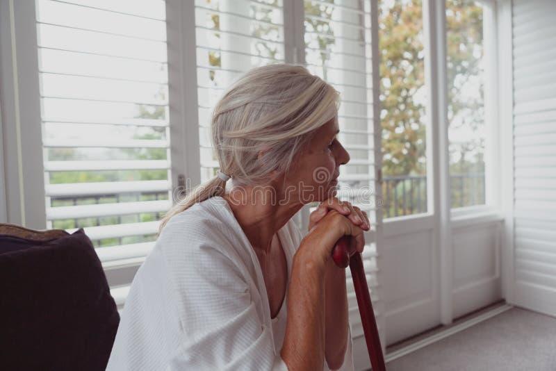 Femme supérieure active se penchant sur la canne de marche et regardant loin dans une maison confortable photos stock