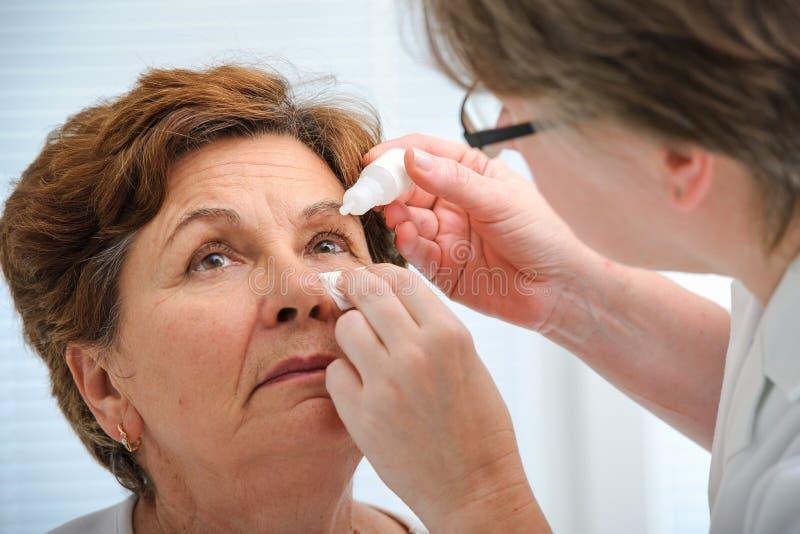 Femme supérieure appliquant des gouttes pour les yeux photo libre de droits