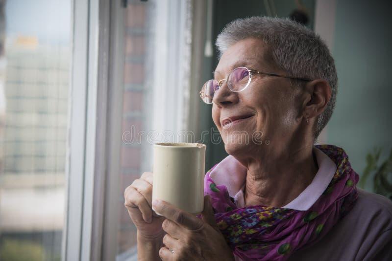 Femme supérieure appréciant la tasse de café photographie stock