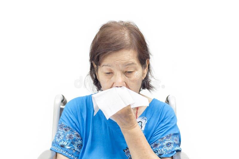 Femme supérieure asiatique soufflant son nez image stock