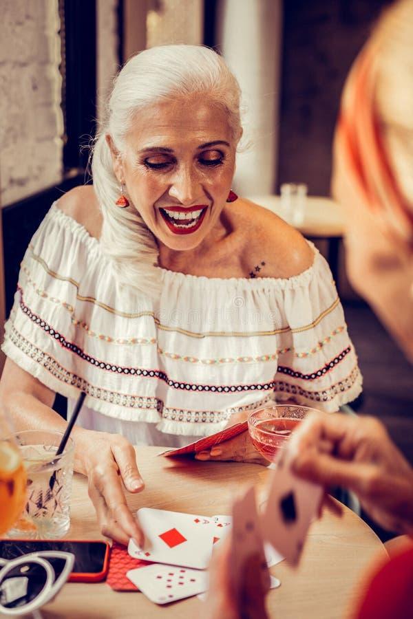 Femme supérieure aux cheveux longs enthousiaste avec le rouge à lèvres lumineux et le dessus blanc photo libre de droits