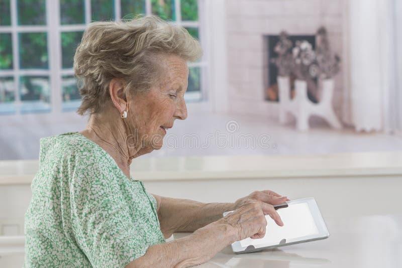 Femme supérieure avec des lunettes passant en revue sur le comprimé numérique photographie stock libre de droits