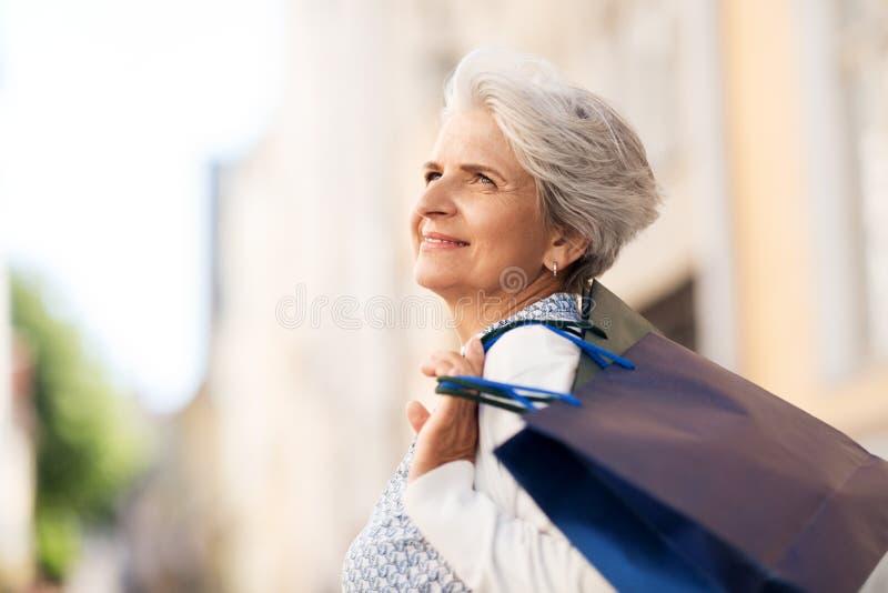 Femme supérieure avec des paniers dans la ville photos libres de droits