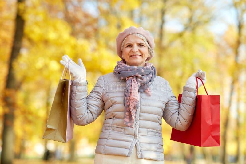 Femme supérieure avec des sacs à provisions au parc d'automne photographie stock