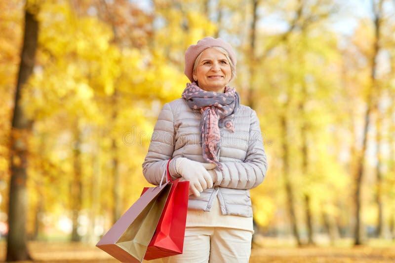 Femme supérieure avec des sacs à provisions au parc d'automne photo stock