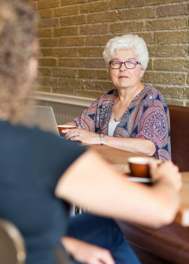 Femme supérieure avec l'ami dans Coffeeshop image libre de droits