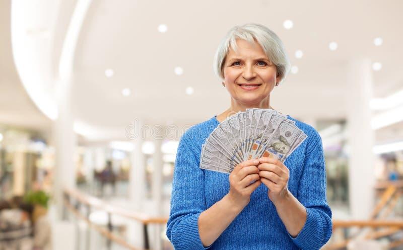 Femme supérieure avec l'argent du dollar au-dessus du centre commercial image libre de droits
