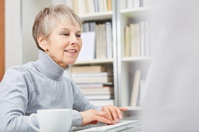 Femme supérieure avec l'ordinateur photographie stock