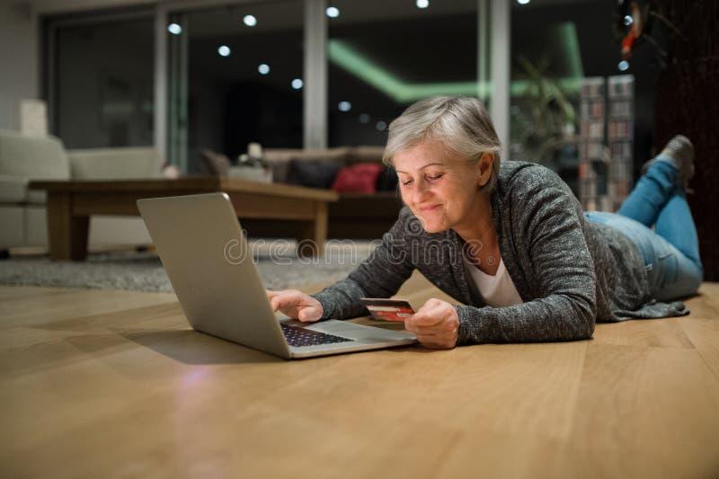 Femme supérieure avec l'ordinateur portable se trouvant sur le plancher faisant des emplettes en ligne images libres de droits